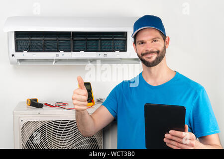Installation service fix  repair maintenance of an air conditioner indoor unit, by cryogenist technican worker giving thumbs up ready to go after comm - Stock Photo