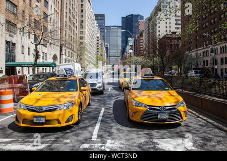 NEW YORK, NY, USA - APRIL 22, 2015:  Yellow cabs on Park Avenue in NYC during spring season. - Stock Photo
