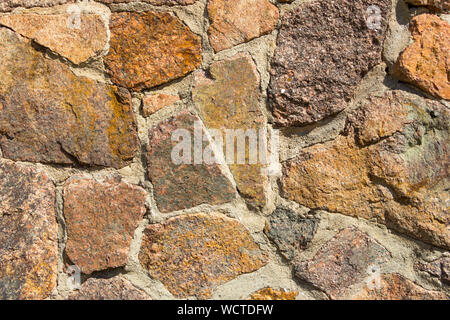 Stone fence texture of decorative masonry with large stones and boulders for an art background. Beautiful rough surface of construction. Old cement in - Stock Photo