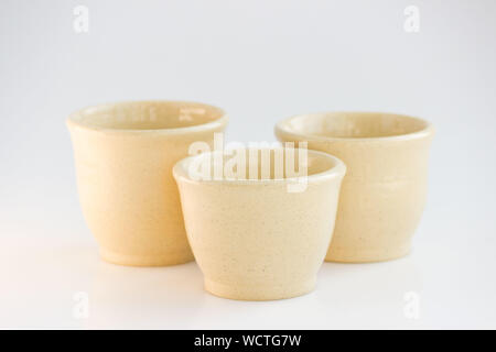 Three beige tea bowls. handwork. cups of different sizes are made on a pottery wheel. - Stock Photo