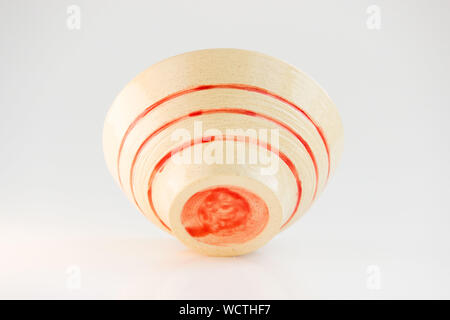 small beige plate with red stripes. handmade. made on a potter s wheel, covered with transparent glaze, burned in a kiln. bottom view - Stock Photo