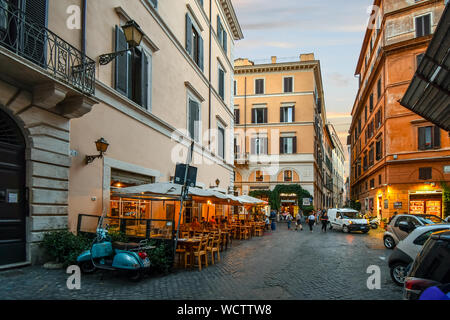 Dusk in the historic center of Rome Italy as tourists and locals enjoy early evening at the sidewalk cafes and shops. - Stock Photo