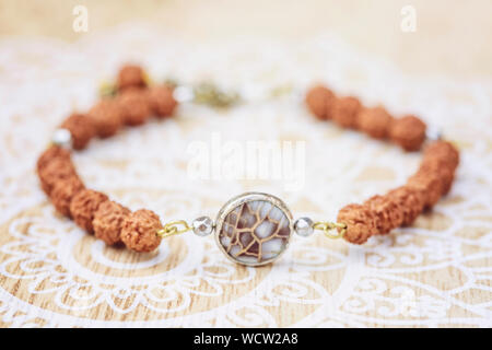 Mother pearl natural bead rudraksha seed bracelet on decorative background - Stock Photo