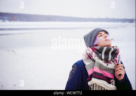 Young Woman Wearing Warm Clothing Smoking During Winter - Stock Photo