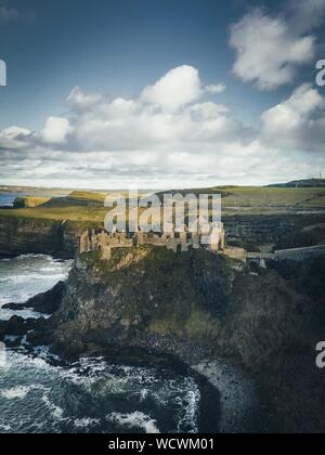 A vertical shot of Dunluce castle on a cliff by the water under a clear sky with white clouds in Ireland - Stock Photo