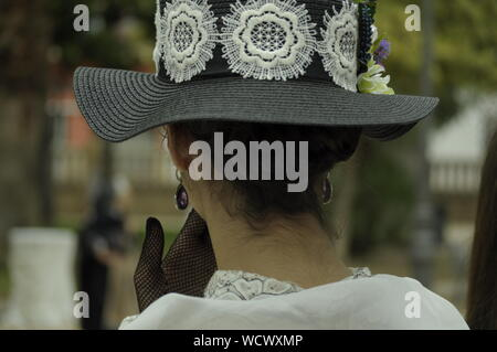 Young lady wearing modernist clothes, with her hand on her mouth. Wearing a big hat with flowers and net gloves. Elegant woman wearing vintage clothes - Stock Photo