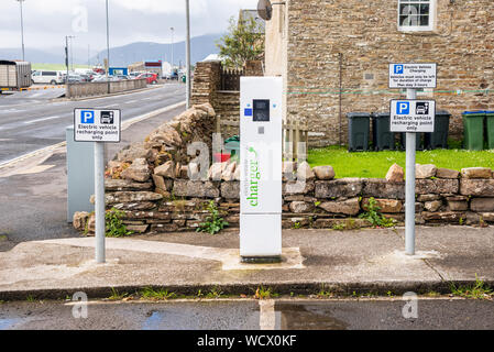 Electric car charging station with a charger and parking signs along a street on a cloudy summer day - Stock Photo