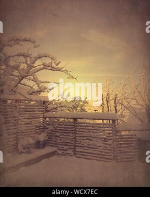 Snow Covered Fence And Field Against Sky During Sunset - Stock Photo