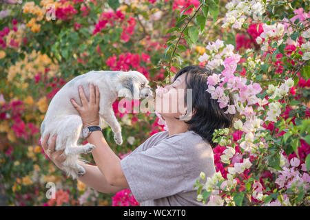 Side View Of Woman With Dog Amidst Plants