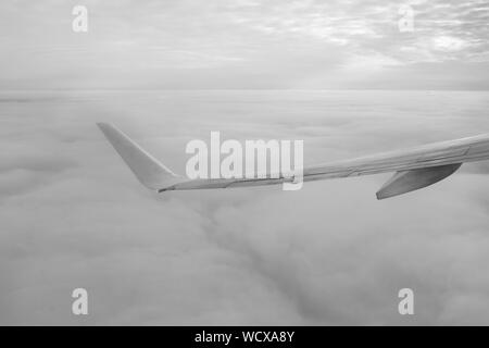 Airplane Wing Flying Over Cloudscape - Stock Photo