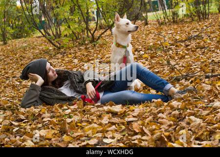 One Teenage Girl Lying On Ground With Dog - Stock Photo
