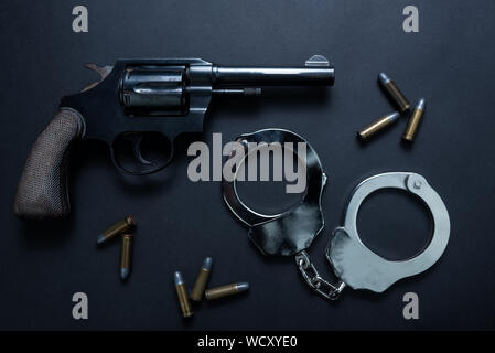 Gun with ammunition and shackle on black background, Top view - Stock Photo