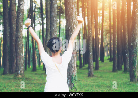 Rear View Of Excited Woman Standing With Arms Raised Against Trees In Forest - Stock Photo