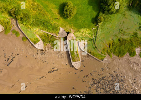 Aerial drone view of silt filled abandoned ships on the banks on a muddy river - Stock Photo