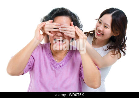 Smiling Daughter Covering Mother Eyes While Standing Against White Background - Stock Photo