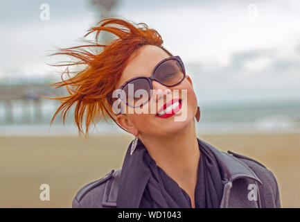 Portrait Of Smiling Young Woman Wearing Sunglasses Against Sky - Stock Photo
