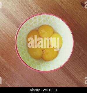 Directly Above View Of Egg Yolk In Bowl On Table - Stock Photo