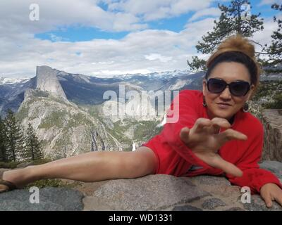 Portrait Of Smiling Woman Climbing Rock At Yosemite Valley Against Half Dome - Stock Photo