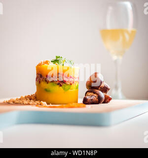Peruvian Dish, Causa Limeña with Toasted Mushrooms, accompanied by a Glass of Wine - Stock Photo