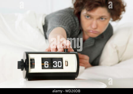 Woman In Bed Reaching Out To Alarm Clock - Stock Photo