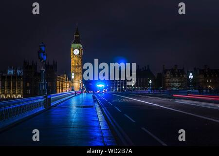 Light Trails On Westminster Bridge By Illuminated Big Ben Against Sky At Night - Stock Photo