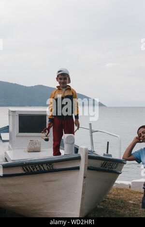 Portrait Of Boy Standing On Boat At Shore Against Mountains And Sky - Stock Photo
