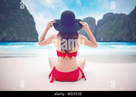 Rear View Of Woman Wearing Red Bikini While Sitting On Shore At Beach - Stock Photo