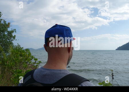 Rear View Of Man Wearing Cap By Sea Against Sky - Stock Photo