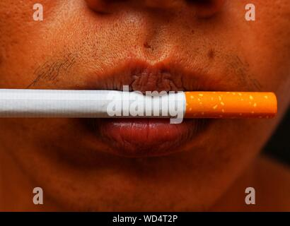Cropped Image Of Young Man With Cigarette In Lips - Stock Photo