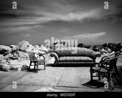 Empty Sofa And Chairs On Footpath Against Sky