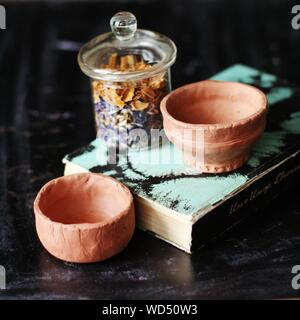 Close-up Of Ceramic Bowls And Book On Table - Stock Photo