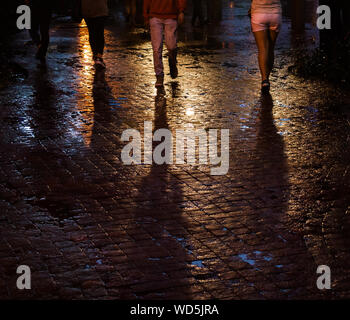 Low Section Of People Walking On Wet Street - Stock Photo
