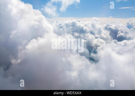 White clouds on blue sky background close up, cumulus clouds high in azure skies, sunny heaven landscape, beautiful aerial cloudscape view from above - Stock Photo