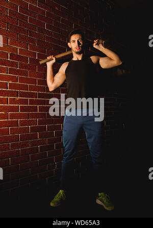 Portrait Of Man Holding Hammer While Standing By Brick Wall At Night - Stock Photo