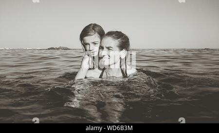 Mother Carrying Daughter While Swimming In Sea Against Clear Sky - Stock Photo