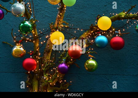 Low Angle View Of Christmas Decorations Hanging On Tree Against Wall - Stock Photo