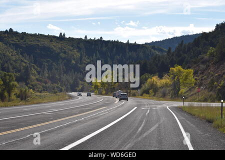 Cars On Country Road Leading Towards Mountains Against Sky - Stock Photo