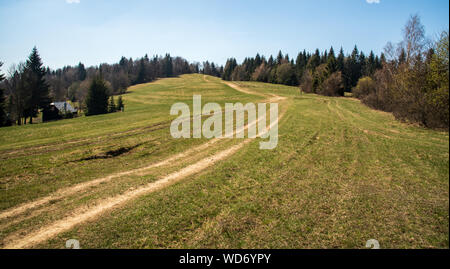 springtime mountain meadow with dirty road, trees around, isolated house and clear sky in Javorniky mountains in Slovakia - Stock Photo