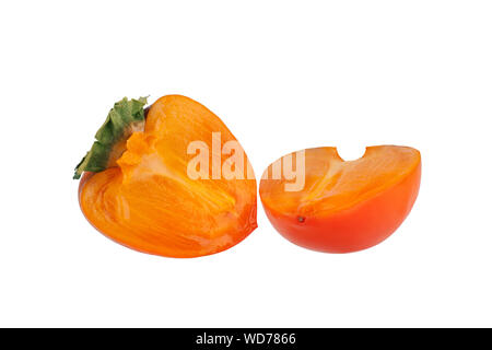 Persimmon fruit or diospyros kaki with green leaves sliced in two halves on white background isolated close up - Stock Photo