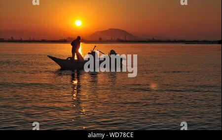 Silhouette Men On Boat In Sea Against Sunset Sky - Stock Photo