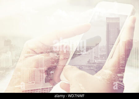 Digital Composite Image Of Hand Holding Mobile Phone Against Cityscape - Stock Photo
