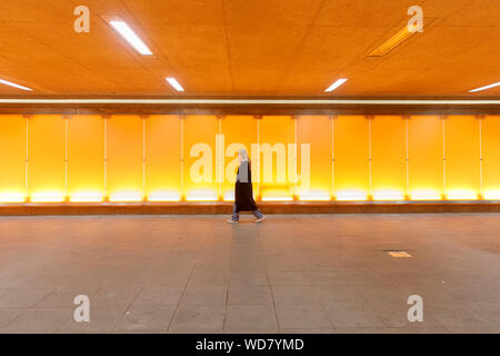 Young woman walking through underpass in Arlanda Airport, Sweden - Stock Photo