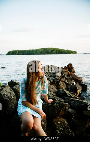 Portrait of young woman with lake in background - Stock Photo