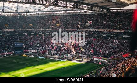 FRANKFURT AM MAIN, GERMANY - Aug 01, 2019: A beautiful shot of the people sitting in the football stadium cheering - Stock Photo