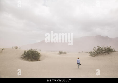 Rear View Of Woman Walking On Sand Dune Against Cloudy Sky At Death Valley National Park - Stock Photo