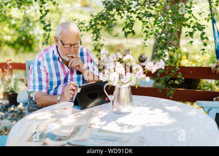 Senior man using tablet PC at outdoor table - Stock Photo