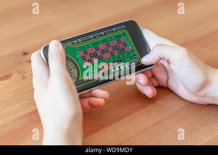 London / UK, August 24th 2019 - Closeup of hands gambling on mobile phone device, with a shallow depth of field. - Stock Photo