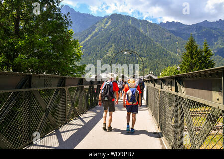 Tourists and hikers crossing a pedestrian bridge over the railway with the mountains in the background in summer, Chamonix-Mont-Blanc, Alps, France
