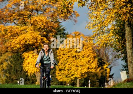 Teenage Boy Riding Bicycle Against Autumn Trees On Field - Stock Photo