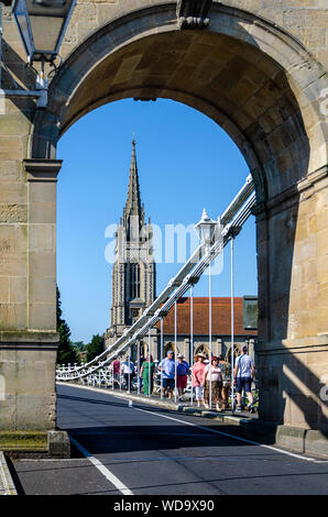 All Saints Church in Marlow seen though the archway of one of the support towers of Marlow Suspension Bridge which spans The River Thames at Marlow. - Stock Photo